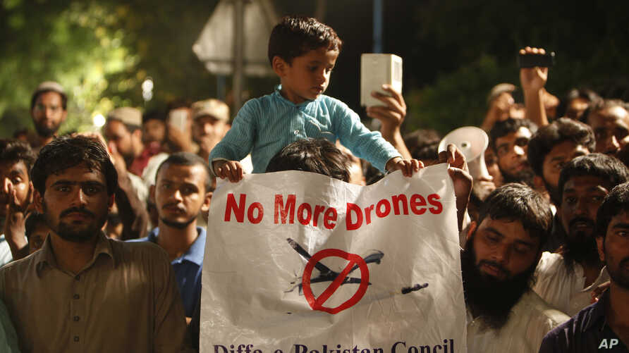 FILE - A boy holds a banner while sitting on his father's shoulder attending a rally called by Pakistan Defense Council, a coalition of Islamic parties, in Lahore, Pakistan, June 12, 2016. Hundreds of supporters of an Islamic parties alliance rallied...