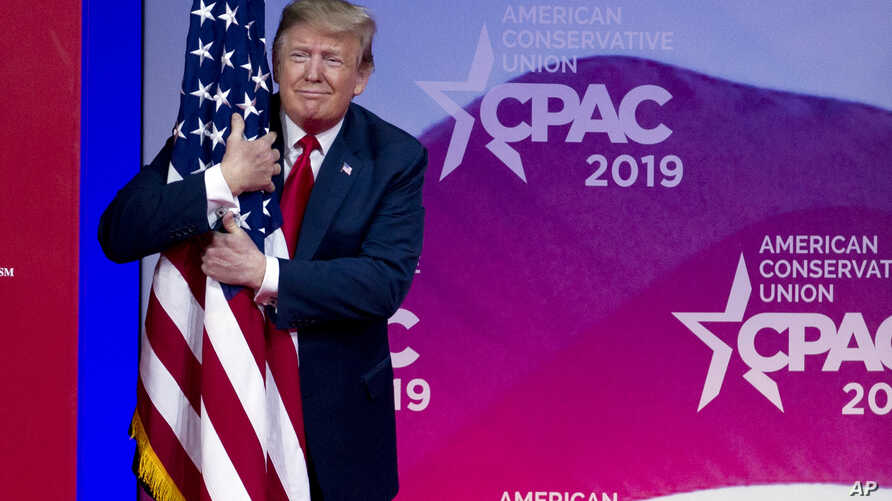 President Donald Trump hugs the American flag as he arrives to speak at Conservative Political Action Conference, in Oxon Hill, Md., March 2, 2019.