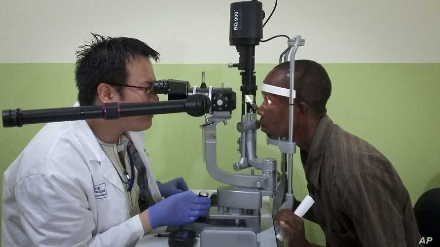 Dr. Zan Yeong, an eye specialist for a joint Liberian-American Ebola initiative known as the Partnership for Research on Ebola Vaccine in Liberia (PREVAIL), examines the eyes of Ebola survivor Abraham Moses, who has problems with his vision, at the J