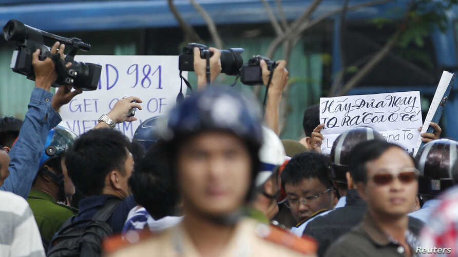 """Police and security personnel film protesters holding placards which read, """"Haiyang 981 oil rig get out of Vietnam (L)"""" and """"Take China to the international court"""" (R)"""
