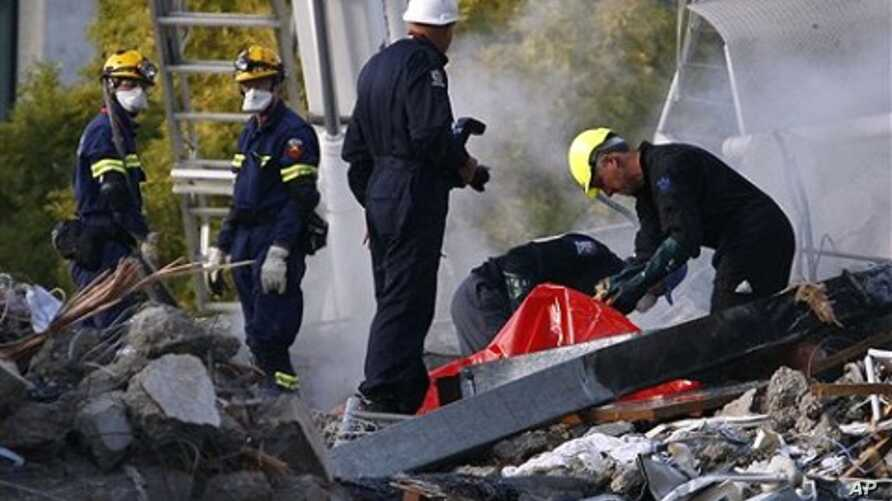 Emergency workers prepare to remove a body from the site of the CTV building in Christchurch, New Zealand,  February 24, 2011, after the city was hit by a 6.3 magnitude earthquake Tuesday.