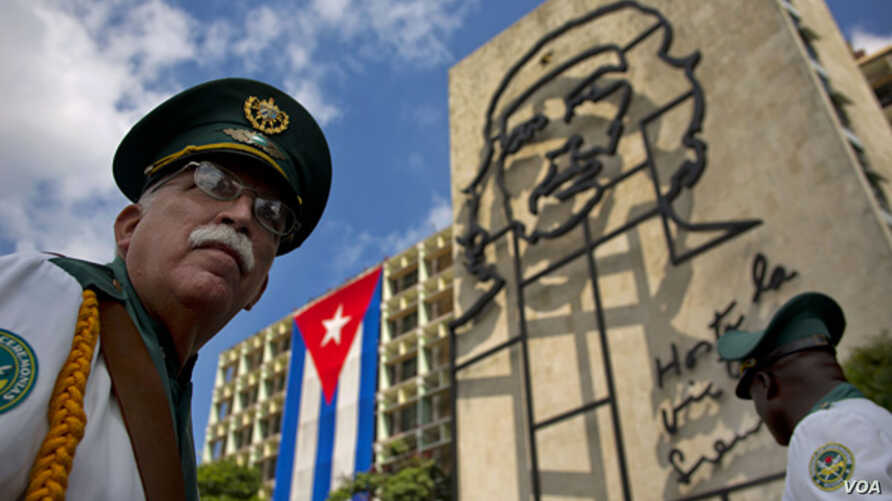 """FILE - Members of a military band stand under the iron sculpture of Ernesto """"Che"""" Guevara at Revolution Square in Havana, Cuba"""