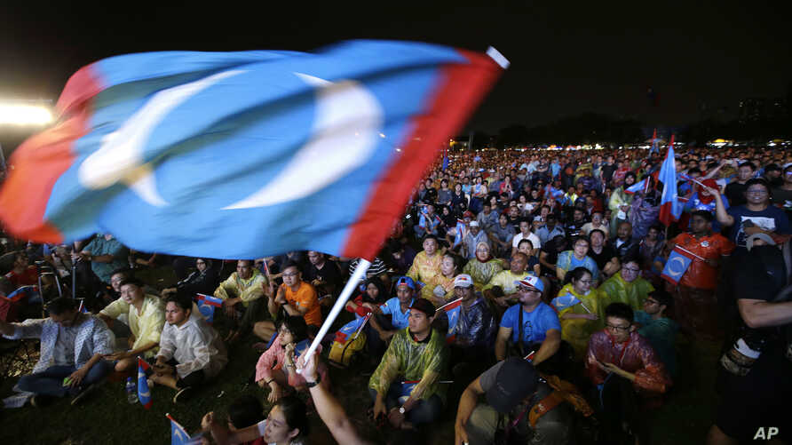 In this May 6, 2018 photo, supporters of former Malaysian strongman Mahathir Mohamad wave flag during an election campaign in Kuala Lumpur, Malaysia.