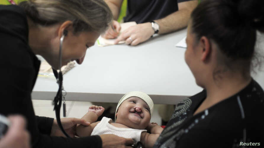 A doctor examines a cleft-lipped baby during a medical evaluation provided by Operation Smile volunteers at San Felipe hospital in Tegucigalpa November 14, 2012. Operation Smile is a charity organization that aims to provide free surgery for children
