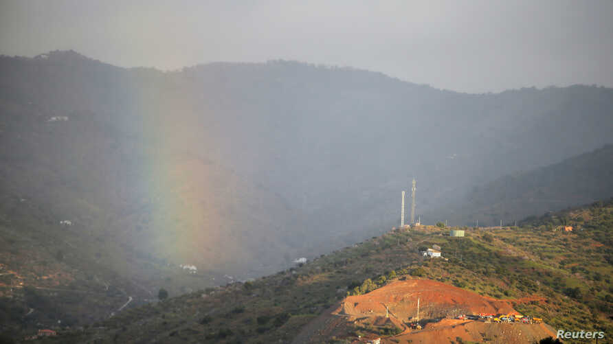 A rainbow appears over a mountain as a drill, bottom right, works where Julen Rosello, a 2-year-old Spanish boy, fell into a deep well earlier in the month when the family was taking a stroll through a private estate, in Totalan, southern Spain, Jan.