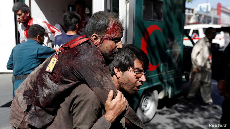An Afghan man carries an injured man to a hospital after a blast in Kabul, Afghanistan May 31, 2017.