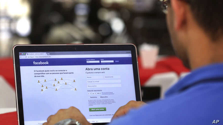 FILE - In this Jan. 4, 2018, file photo, a man demonstrates how he enters his Facebook page as he works on his computer in Brasilia, Brazil. Facebook is once again tweaking the formula it uses to decide what people see in their news feed.