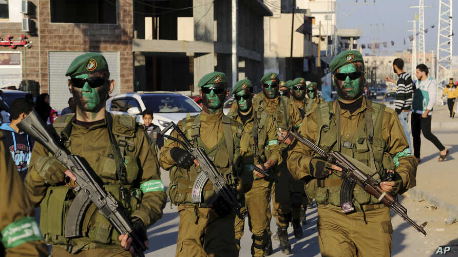 FILE - Masked militants from the Izzedine al-Qassam Brigades, a military wing of Hamas, paint their faces with green color while marching along the streets of Nusseirat refugee camp, Central Gaza Strip, Thursday, Jan. 19, 2017.
