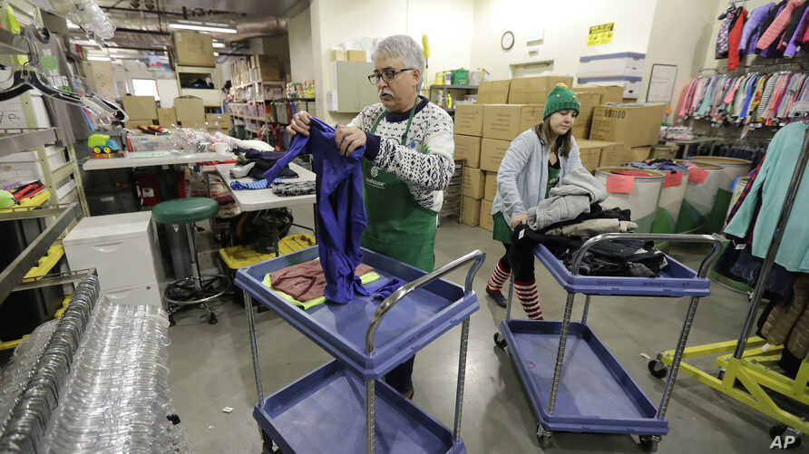 In this Friday, Dec. 21, 2018, photo, Chris Meyer, left, and Maddi Heim, fold and sort donated clothes at Treehouse, a nonprofit organization in Seattle that serves the needs of children in the foster-care system.