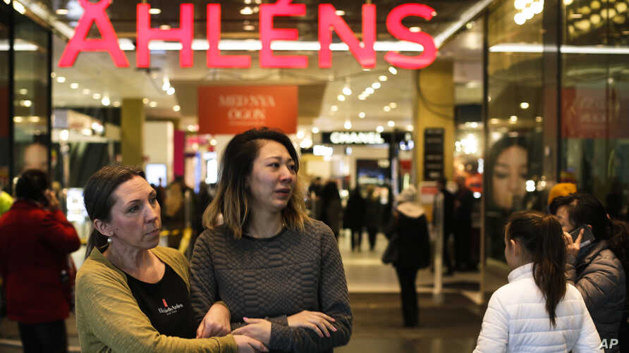 People exit and enter the reopened department store Ahlens in Stockholm, Sweden, April 10, 2017.