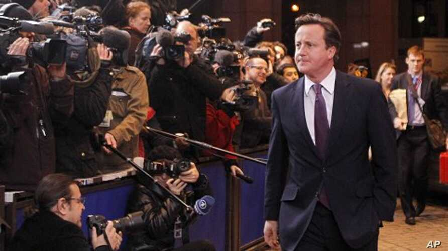 British Prime Minister David Cameron, center, speaks with the media as he arrives for an EU summit in Brussels, Dec. 8, 2011.