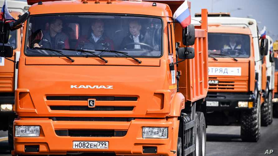 Russian President Vladimir Putin (C-R) drives a truck to officially open the much-anticipated bridge linking Russia and the Crimean peninsula, during the opening ceremony near in Kerch, Crimea, May 15, 2018.