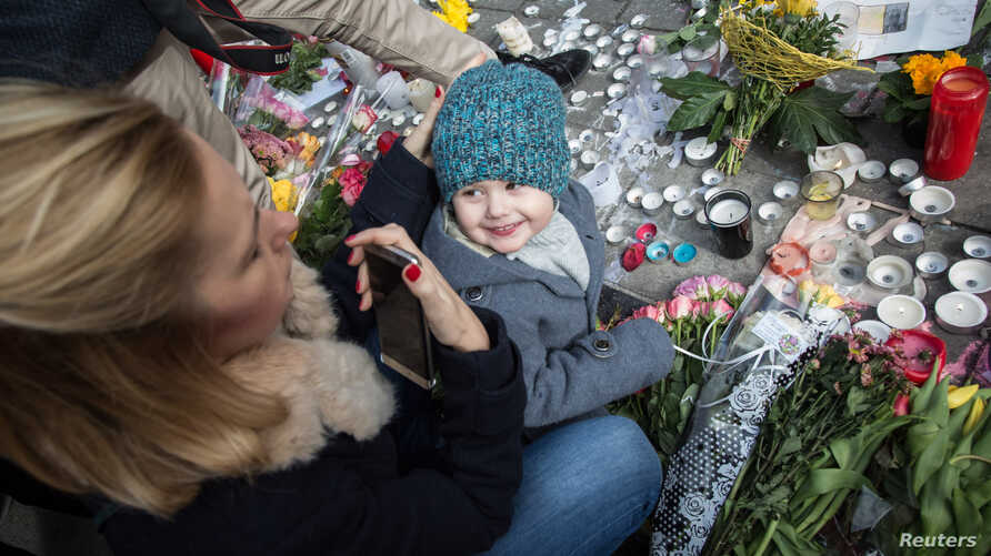A woman looks at her daughter on the Place de la Bourse in central Brussels, on March 23, 2016 as people gather to observe a minute of silence in memory of the victims of the Brussels airport and metro bombings.