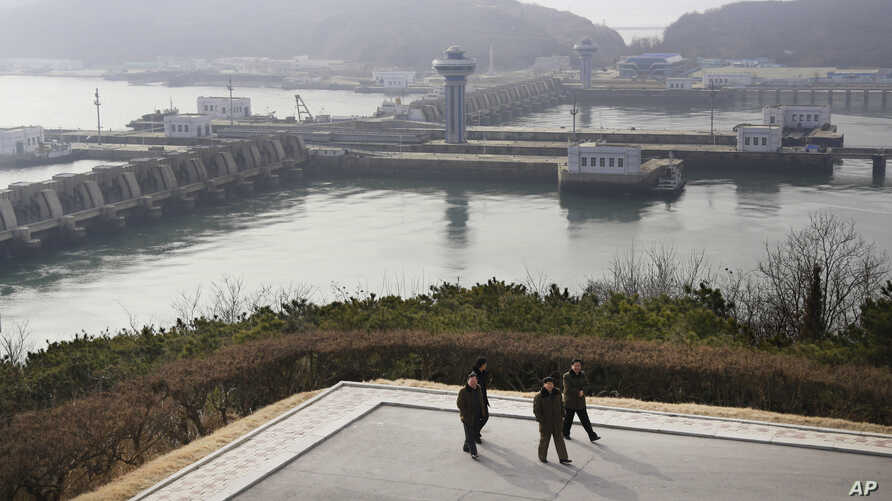 North Koreans men walk with the West Sea Barrage in the background in Nampo, North Korea, Feb. 2, 2019.