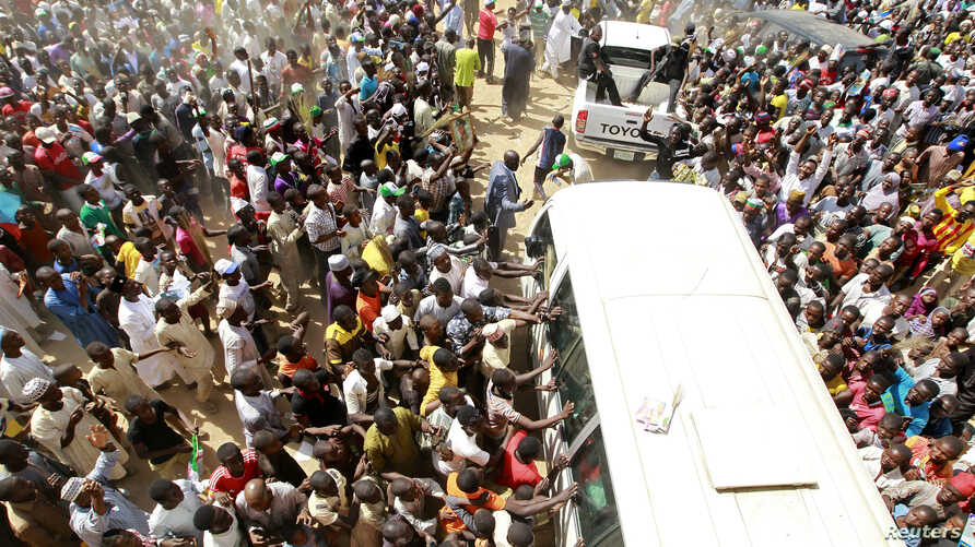 Supporters welcome Muhammadu Buhari (in vehicle), presidential candidate from the All Progressives Congress party, as he visits Gombe Emir Abubakar Shehu-Abubakarn at the emir's palace during an election rally in Gombe February 3, 2015. Buhari has pl