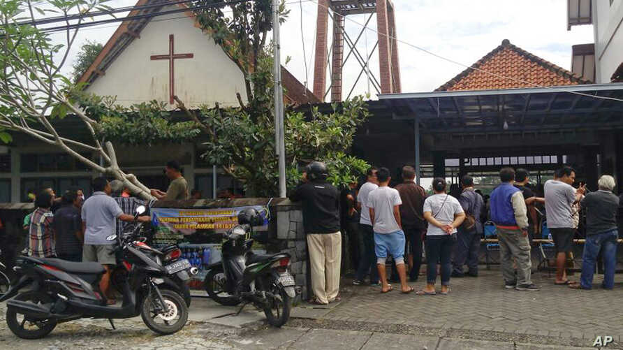 Onlookers gather outside of St. Lidwina Church following an attack in Sleman, Yogyakarta province, Indonesia, Feb. 11, 2018. Police shot a sword-wielding man who attack the church during a mass, injuring a number of people.