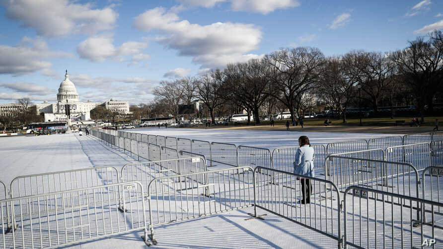 A pedestrian stand at the intersection of barricades dividing areas of standing room on the National Mall in Washington, Jan. 18, 2017, as preparations continue for Friday's presidential inauguration.