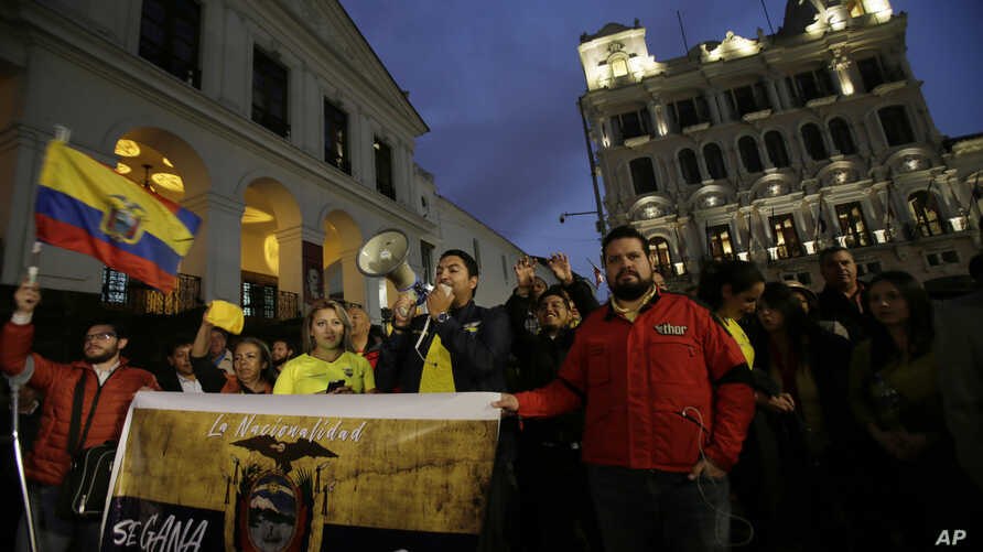 "FILE - Protesters demand the government remove Julian Assange's Ecuadorean nationality, carrying a sign that reads in Spanish ""Nationality is earned, not given away,"" outside the government palace in Quito, Ecuador, Oct. 31, 2018."