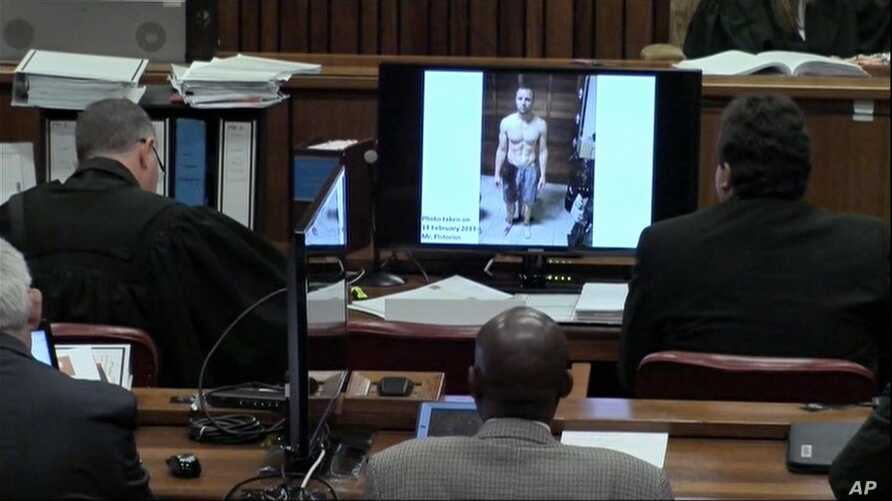 An image taken from the court pool TV via AP showing on screen a police photograph of Oscar Pistorius standing on his blood-stained prosthetic legs and wearing shorts covered in blood, taken shortly after the athlete fatally shot his girlfriend, whic