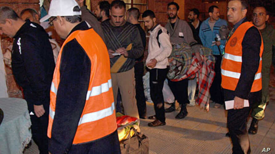 Arab league observers wearing orange vests oversee the releasing of Syrian prisoners who wait in queue to be released from Adra Prison on the outskirts of Damascus,  January 15, 2012