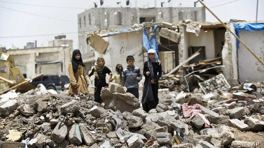 A boy and his sisters watch graffiti artists spray on a wall, commemorating the victims who were killed in Saudi-led coalition airstrikes in Sanaa, Yemen, May 18, 2015.