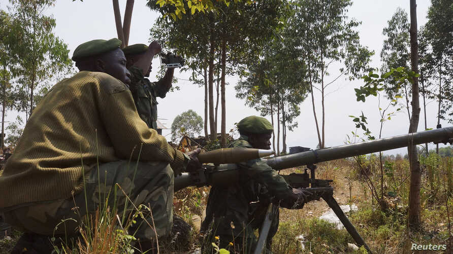 Congolese government army soldiers prepare their weapons at an attack position near Munigi, overlooking the front-line, where they are fighting against M23 rebels outside the eastern Congolese city of Goma, Jul. 15, 2013.