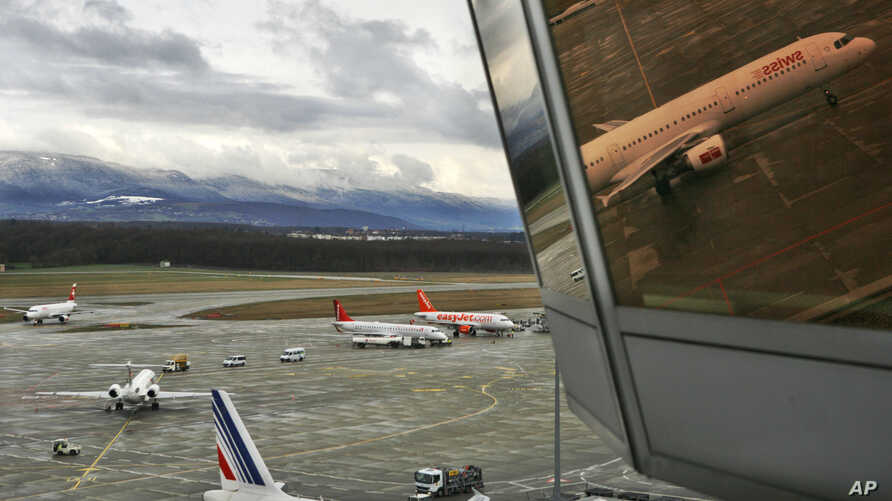 FILE - A passenger plane is reflected in a window of the airport tower as it arrives in Geneva, Switzerland.