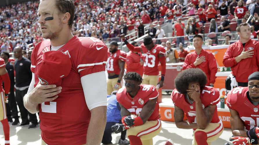 FILE - San Francisco 49ers quarterback Blaine Gabbert, left, stands as Eli Harold, from bottom left, Colin Kaepernick and Eric Reid kneel during the national anthem before an NFL football game against the Dallas Cowboys in Santa Clara, California, on