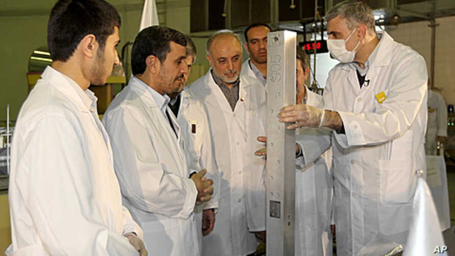 This photo released by the Iranian President's Office, claims to show Iranian President Mahmoud Ahmadinejad, second left being escorted by technicians during a tour of Tehran's research reactor center in northern Tehran, Iran, February 15, 2012.