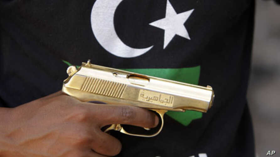 A Libyan National Transitional Council (NTC) fighter holds a golden gun, marked in Arabic al-Jamahiyra (Gadhafi's people's republic)  (File)