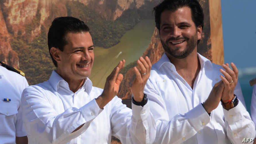 Mexican President Enrique Pena Nieto (L) and Mexican Secretary of Environment and Natural Resources Rafael Pacchiano Alaman applaud during the Thirteenth meeting of the Conference of the Parties (COP13) to the Convention on Biological Diversity (CBD)