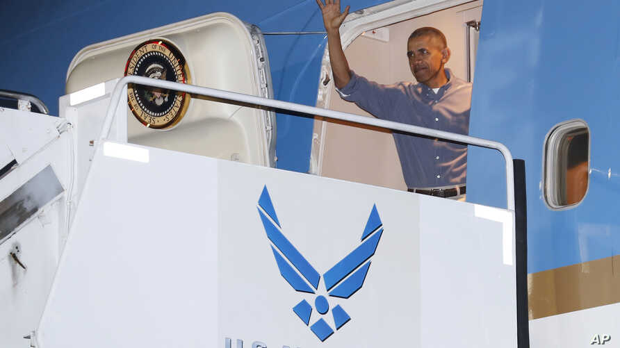 President Barack Obama waves as he arrives on Air Force One, Dec. 16, 2016, in Honolulu, Hawaii, for the annual family vacation on the island of Oahu.