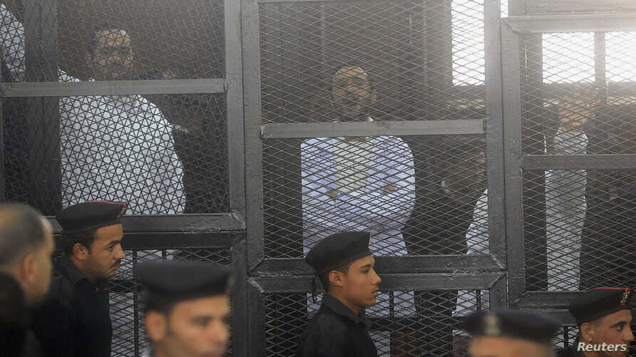 FILE - Political activists Ahmed Maher (R), Ahmed Douma (C) and Mohamed Adel, founder of 6 April movement, look on from behind bars in Abdeen court in Cairo, December 2013.