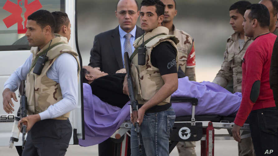 Ousted former Egyptian President Hosni Mubarak is escorted by medical and security personnel into an ambulance at Maadi Military Hospital in Cairo, Egypt, March 2, 2017.