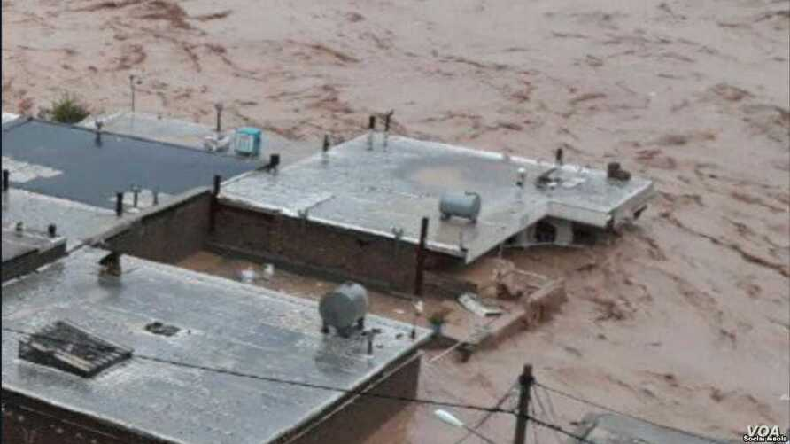 In this image shared on social media and verified by VOA Persian, a flash flood submerges buildings in western Iran's Lorestan province, April 1, 2019.
