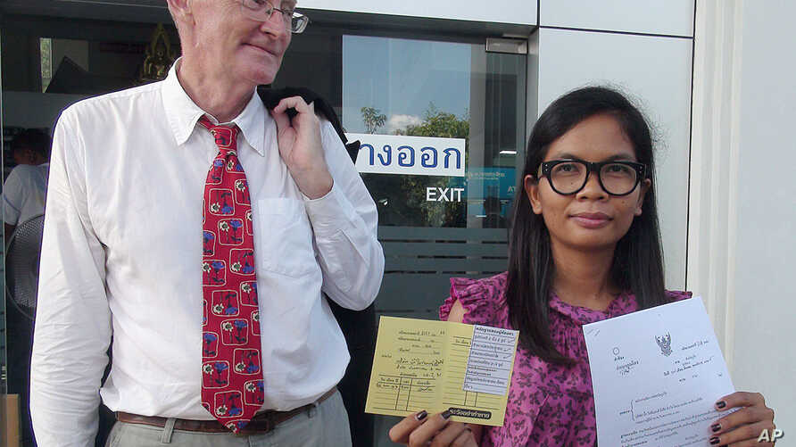 FILE - Alan Morison of Australia, editor of The English-language news website Phuketwan, left, and his Thai colleague, Chutima Sidasathien, right, walk out during a break at Phuket provincial courtroom in Phuket, southern Thailand, Apr. 17, 2014.