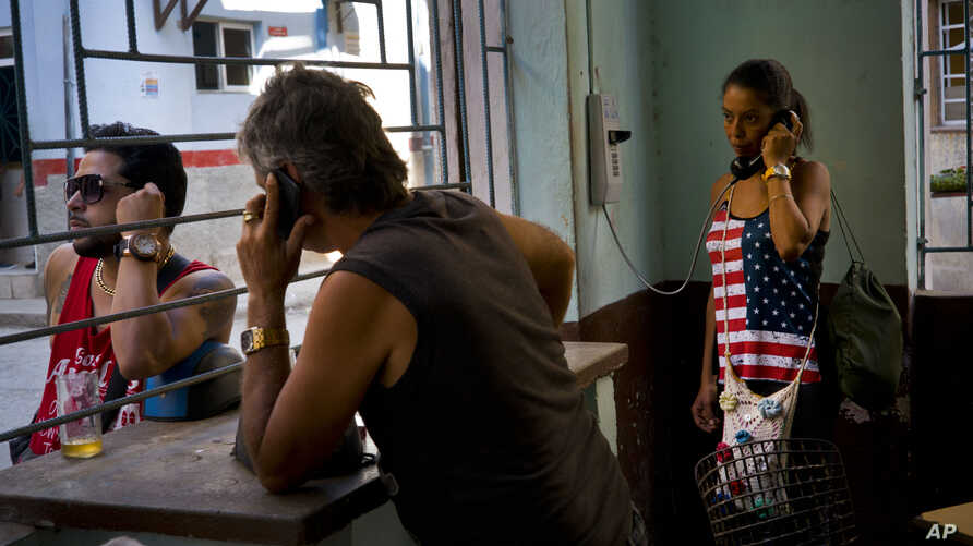 A woman uses the phone at a coffee shop in Havana, Cuba, March 15, 2016. With economic reforms, Cuban consumers can buy cellphones, but only one in four have them.