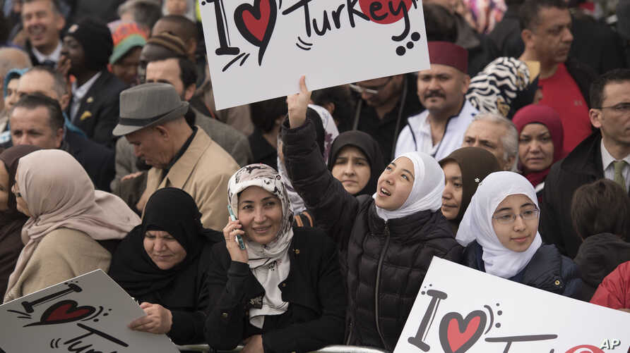 Crowd members hold signs showing support for Turkish President Recep Tayyip Erdogan at the inauguration of the Diyanet Center of America in Lanham, Maryland, April 2, 2016.
