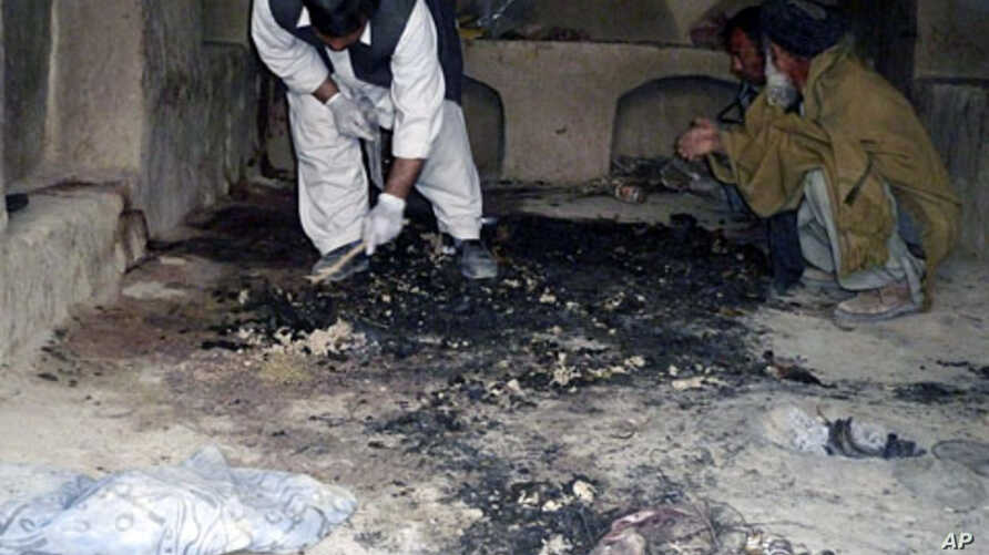 Afghan men investigate the site of a shooting incident in Kandahar province, March 11, 2012