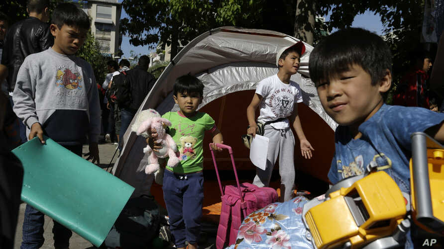Children carry toys and bags leave from their family's tent at Victoria square, where hundreds migrants and refugees stay temporarily before trying to continue their trip to more prosperous northern European countries, in Athens, Oct. 1, 2015.