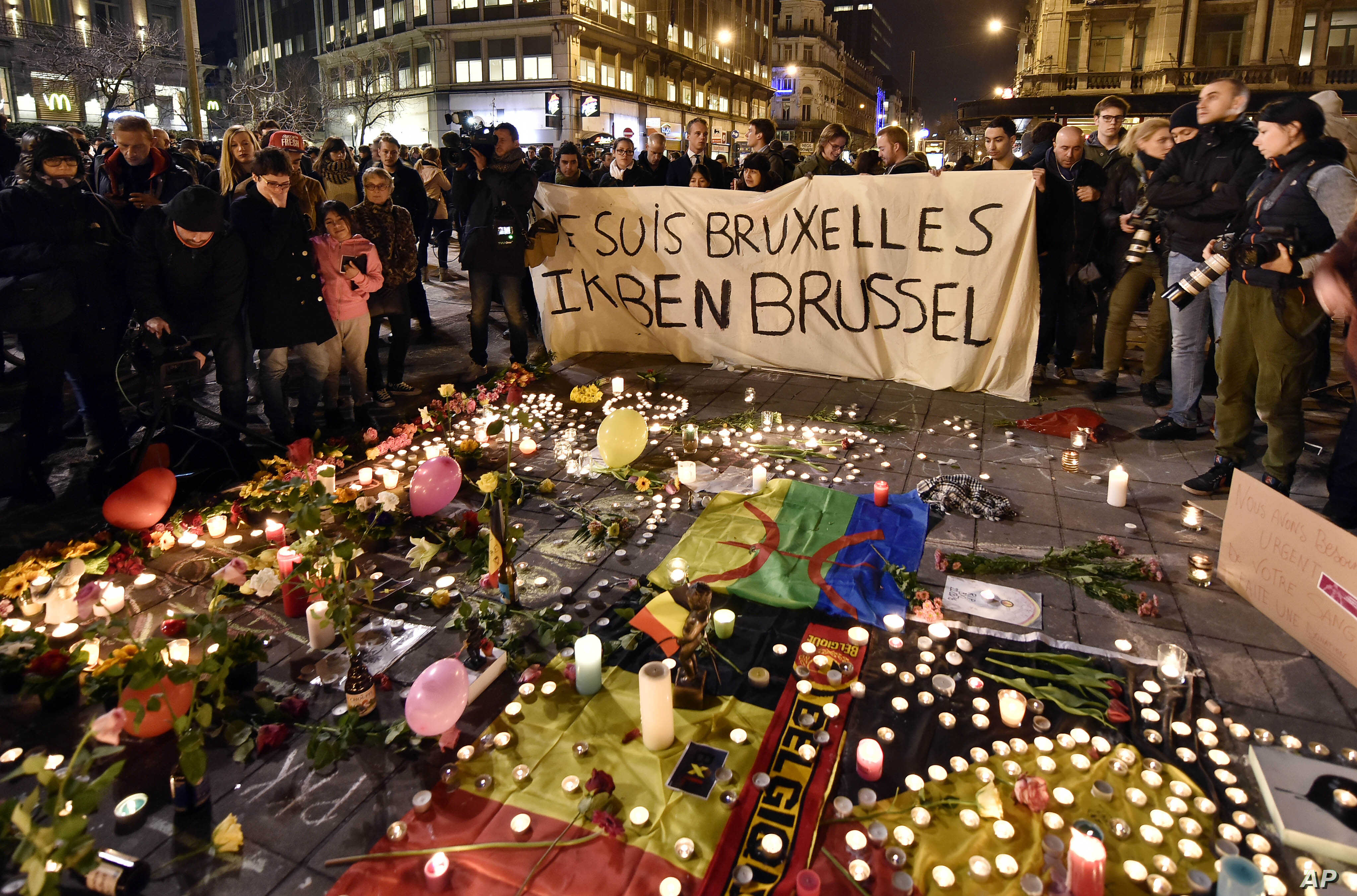 """People hold a banner reading """"I am Brussels"""" behind flowers and candles to mourn for the victims at Place de la Bourse in the center of Brussels, March 22, 2016."""