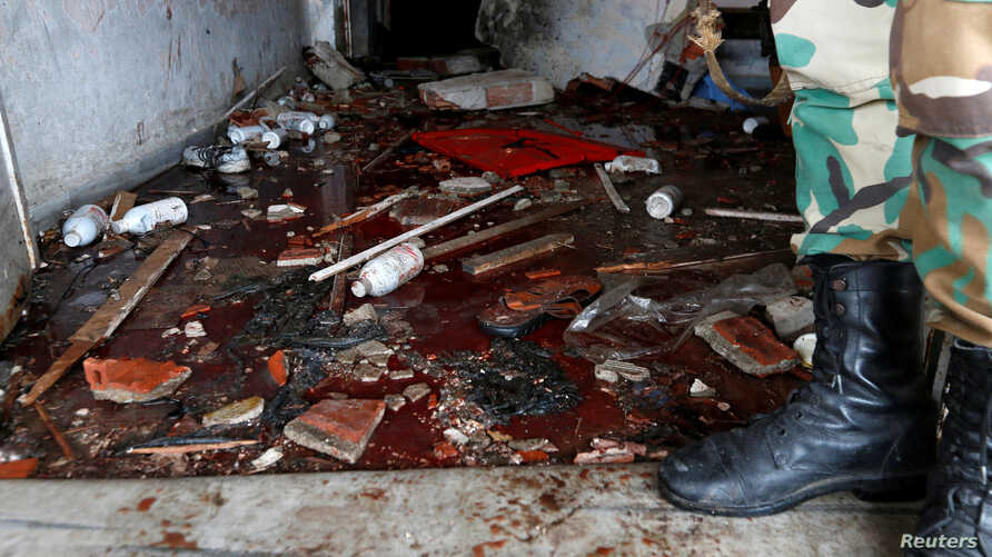 A Syrian Army soldier stands near blood on the ground of a damaged emergency room inside National Hospital after explosions hit the Syrian city of Jableh, May 23, 2016.