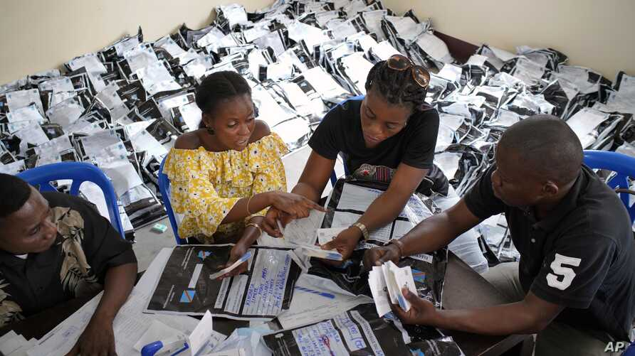 Congolese independent electoral commission (CENI) officials count the presidential ballots from more than 900 polling stations at a local results compilation center in Kinshasa, Congo, Jan. 4, 2019.