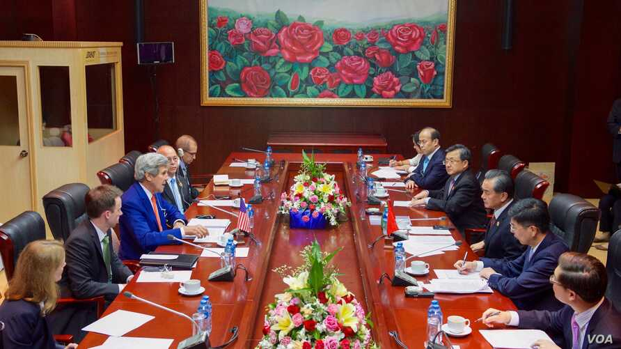 U.S. Secretary of State John Kerry addresses Chinese Foreign Minister Wang Yi and his delegation at the National Convention Center in Vientiane, Laos, on July 25, 2016, during the outset of a bilateral meeting on the sidelines the annual meeting of t