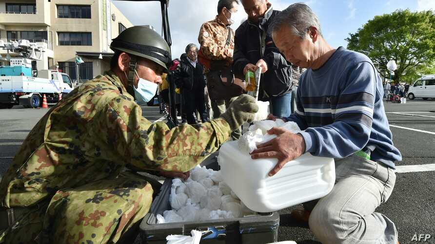 Earthquake-affected evacuees receive rice rations from Japanese Self-Defense Forces personnel at the Mashiki village office in Kumamoto prefecture, April 17, 2016. Rescuers were racing against the weather and the threat of more landslides to try to r