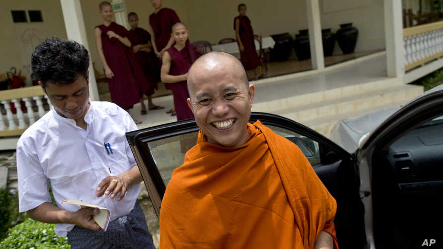 Controversial Buddhist monk Wirathu, foreground, who is accused of instigating sectarian violence between Buddhists and Muslims through his sermons, smiles as he leaves a monastery after an assembly of Burma's powerful Buddhist clergy in Hmawbi, outs