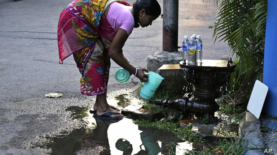 An Indian woman collects water leaking from a safety valve on an underground pipeline on World Water Day in Kolkata, India, March 22, 2017.