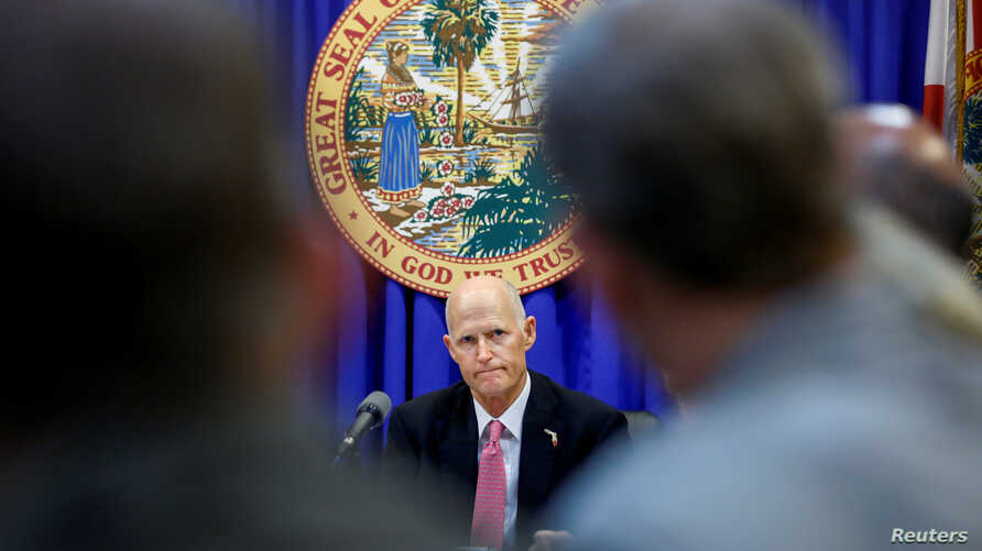 FILE - Florida Governor Rick Scott listens during a meeting with law enforcement, mental health, and education officials about how to prevent future tragedies in the wake the mass shooting at Marjory Stoneman Douglas High School, at the Capitol in Ta