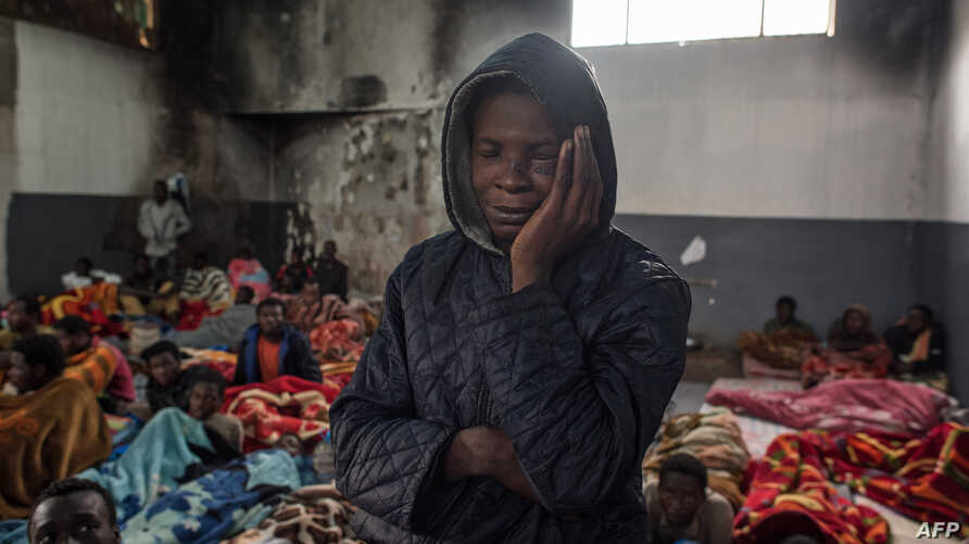 FILE - A migrant holds his head as he stands in a packed room at the Tariq Al-Matar detention center on the outskirts of the Libyan capital Tripoli, Nov. 27, 2017.