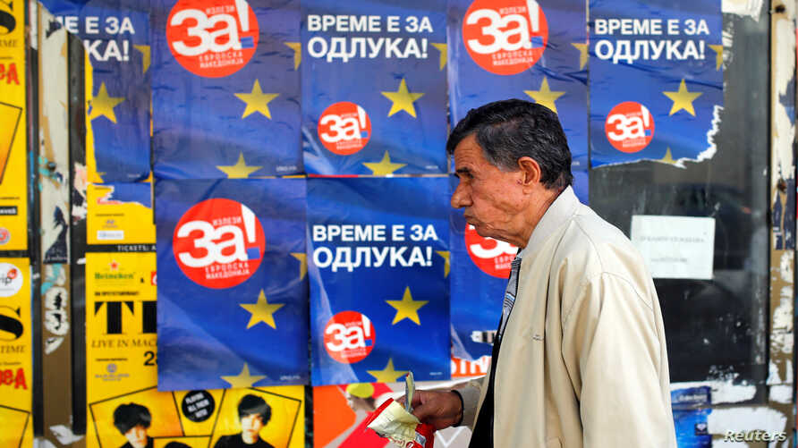 "A man passes posters reading ""yes"" for the referendum in Macedonia on changing the country's name that would open the way for it to join NATO and the European Union, in Skopje, Macedonia, Sept. 28, 2018."